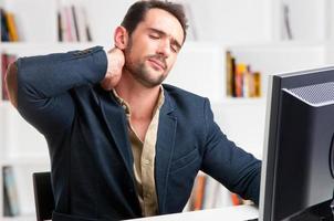 casual zakenman met pijn in zijn nek foto