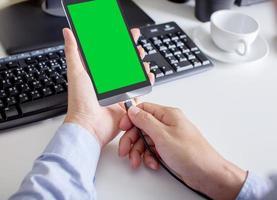 man met de groen scherm telefoon met batterij opladen