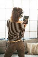 jonge vrouw luisteren muziek in loft appartement. achteraanzicht foto