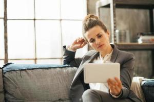 doordachte zakenvrouw met behulp van tablet pc in loft appartement foto