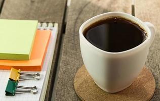 zwarte koffie en notitieboekje, sticker op het bureaublad foto