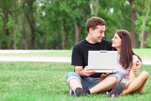 tiener paar met laptop in het park