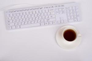 wit toetsenbord en koffiekopje foto
