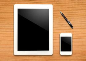 tablet en smartphone met pen op tafel foto