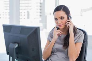 doordachte aantrekkelijke zakenvrouw met een telefoongesprek