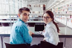 jonge studenten studeren met tablet pc in de bibliotheek foto