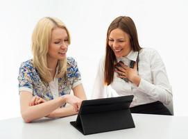 twee vrouwelijke ondernemers bijeen in kantoor met tablet pc. foto