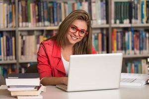 jonge student met behulp van haar laptop in een bibliotheek foto