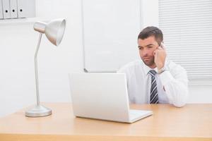 zakenman aan de telefoon met behulp van zijn laptop op balie foto