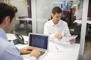 twee zakenlieden werken op kantoor met laptop en tablet pc foto