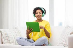gelukkig Afrikaanse vrouw met tablet pc en koptelefoon foto
