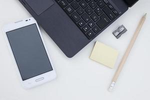 werkruimte met laptop, mobiel, clips, potlood, post het over wit foto
