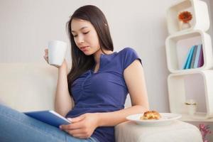 Aziatische vrouw met behulp van haar tablet-pc en koffie te houden foto