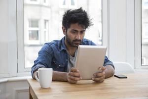 Aziatische man zit aan een tafel lezen van een tablet-pc.
