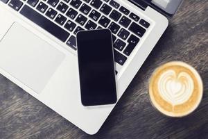 laptop, smartphone en cappuccino op een houten tafel foto