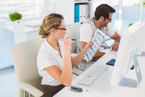 blonde redacteur die over contactblad kijkt bij haar bureau foto