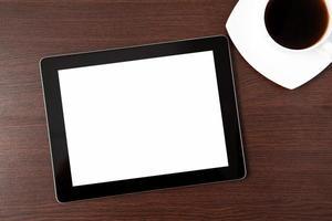 tablet en een dop van caffe op tafel foto