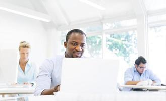 een Afrikaanse zakenman die met zijn laptop werkt foto