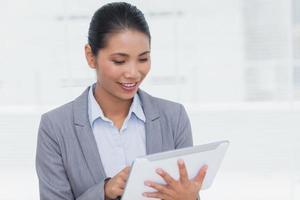 Glimlachende zakenvrouw met behulp van haar tablet-pc foto