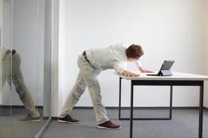 oefenen tijdens kantoorwerk - man met tablet in zijn kantoor foto