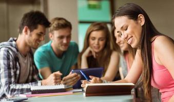 lachende vrienden zitten studeren en het gebruik van tablet pc