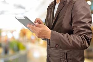 jonge man handen met tablet in winkelcentrum foto