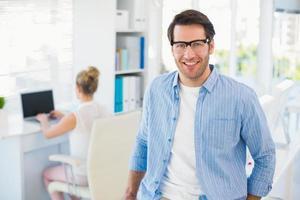 portret van glimlachende fotoredacteur die leesbril draagt foto