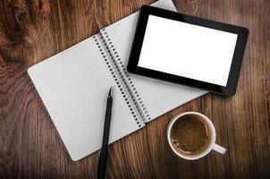 een tablet, koffiemok, pen en notitieblok op een houten tafel