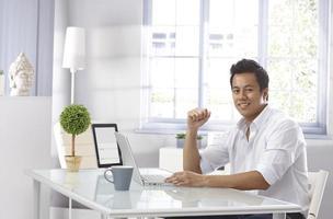 een jonge man met zijn laptop bij hem thuis foto
