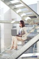 vrouw zittend op de trap met behulp van laptop foto