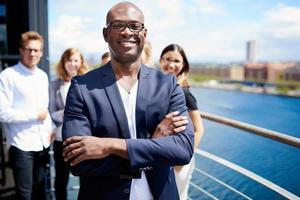 zwarte mannelijke uitvoerende die zich voor collega's bevindt foto