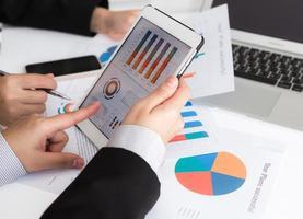 business team analyseren van bedrijfsmodellen met behulp van digitale tablet foto