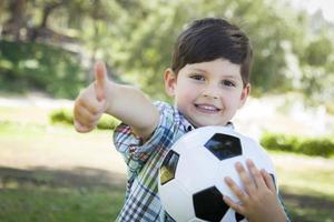 schattige jonge jongen spelen met voetbal in park foto