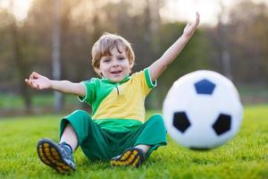 blonde jongen van 4 voetballen met voetbal onl veld foto