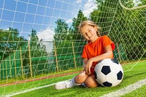 lachende meisje met buigende arm op voetbal zitten foto