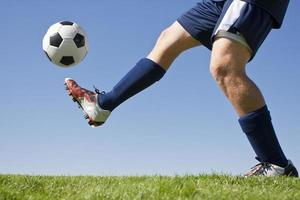 voetballer en groen gras schoppen een voetbal omhoog foto