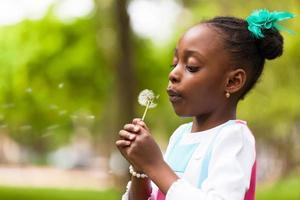 schattig jong zwart meisje met een paardebloem foto