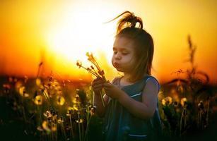 klein meisje onder paardebloemen bij zonsondergang