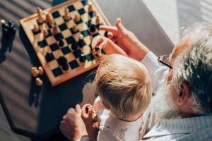 opa leert zijn kleinzoon schaken foto