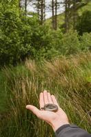 vrouwelijke hand die ouderwets kompas houdt dat de weg toont foto