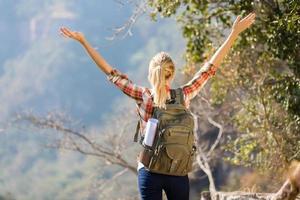 jonge wandelaar armen open op de top van de berg foto
