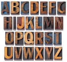 alfabet antieke houten stempels in hoofdletters foto