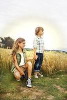 broer en zus plezier in het tarweveld foto