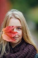 jonge vrouw met herfstbladeren op het hoofd. foto