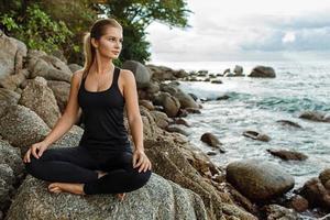 vrouwen die yoga doen met de oceaan erachter foto