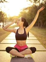 jonge Aziatische vrouw het beoefenen van yoga buiten bij zonsondergang foto