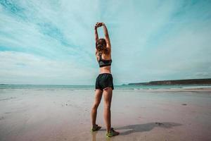 jonge atletische vrouw die zich uitstrekt op het strand foto