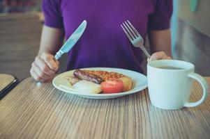 vrouw die van traditioneel Engels ontbijt geniet