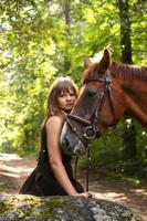 mooi meisje en bruin paard portret in mysterieuze bos foto