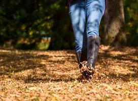 vrouw genieten van de herfstbladeren foto